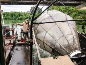 Dean Toba, a biologist with the Washington Department of Fish and Wildlife, operates the agency's screw trap on the Skagit River. The trap helps biologists estimate the number of juvenile salmon leaving the river each year. Photo: Christopher Dunagan, PSI