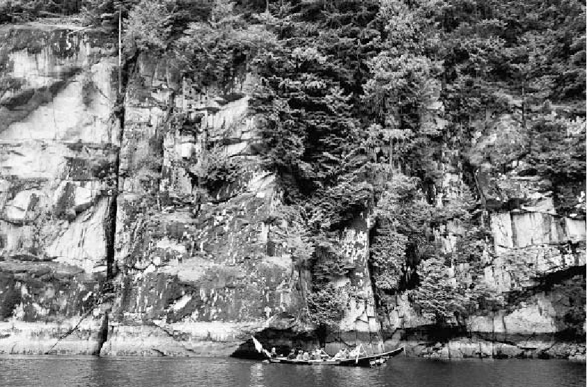 Tsleil-Waututh canoe travel in Indian Arm at DiRr-6, a massive outcrop of intrusive granodioritic rock marked with a single painting, 2014. Most rock paintings were meant to be seen in this context. Photo by Jesse Morin